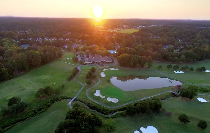 Drone photography of Polo Fields Golf and Country Club clubhouse at sunset.